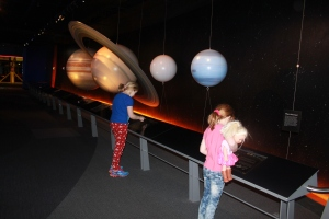 The  girls comparing weights on various planets at the Adventure Science Center